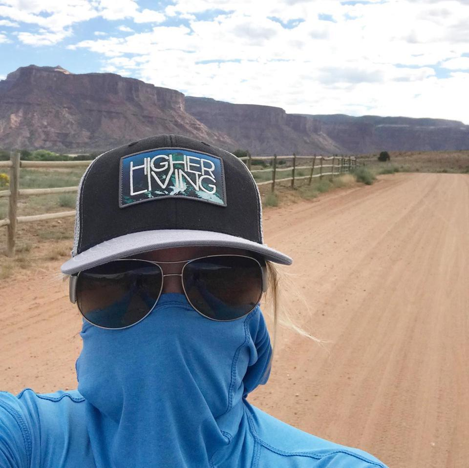 Woman wearing a face-covering, baseball cap and sunglasses.