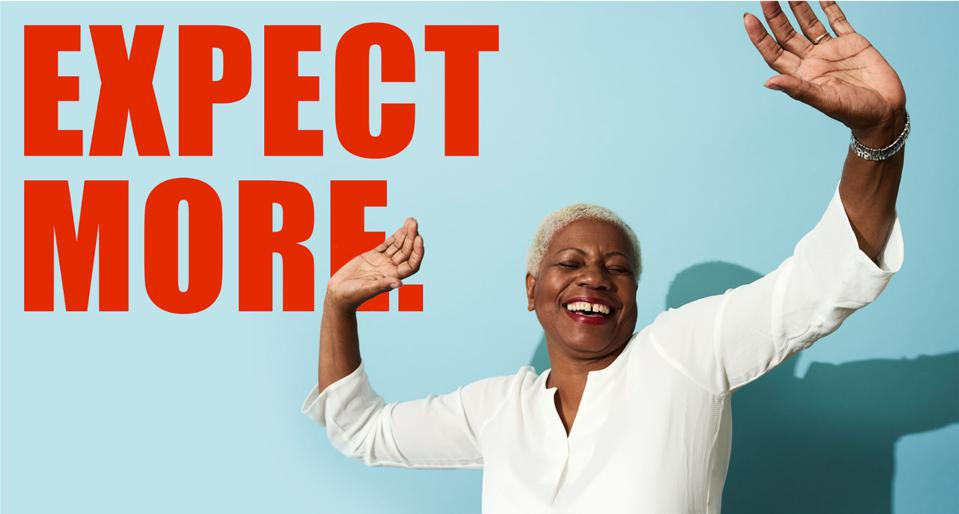 Joyous woman with hands in the air. Bold ″Expect More″ text shows MMRF's refreshed brand.