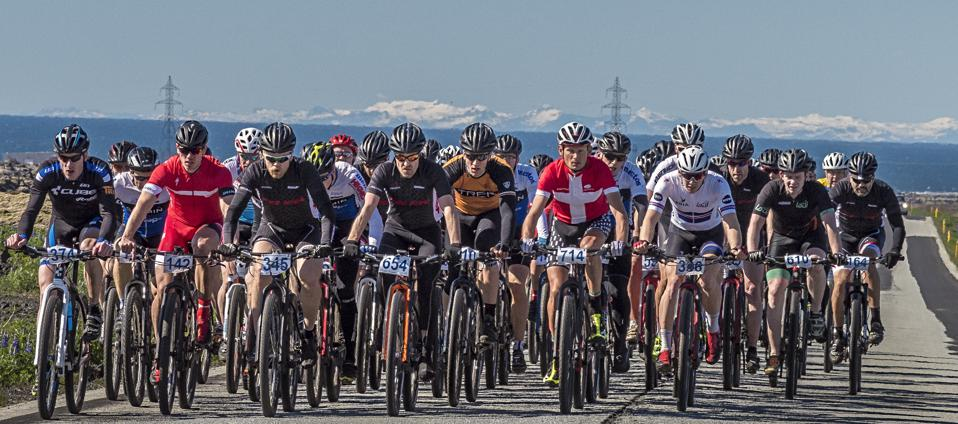a wall of racing cyclists scale a hill with ocean in the background