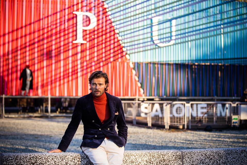 Alessio Piastrelli, wearing Brunello Cucinelli corduroy blue blazer and white corduroy pants, and orange turtleneck outside the Pitti Uomo trade show in  Florence, Italy