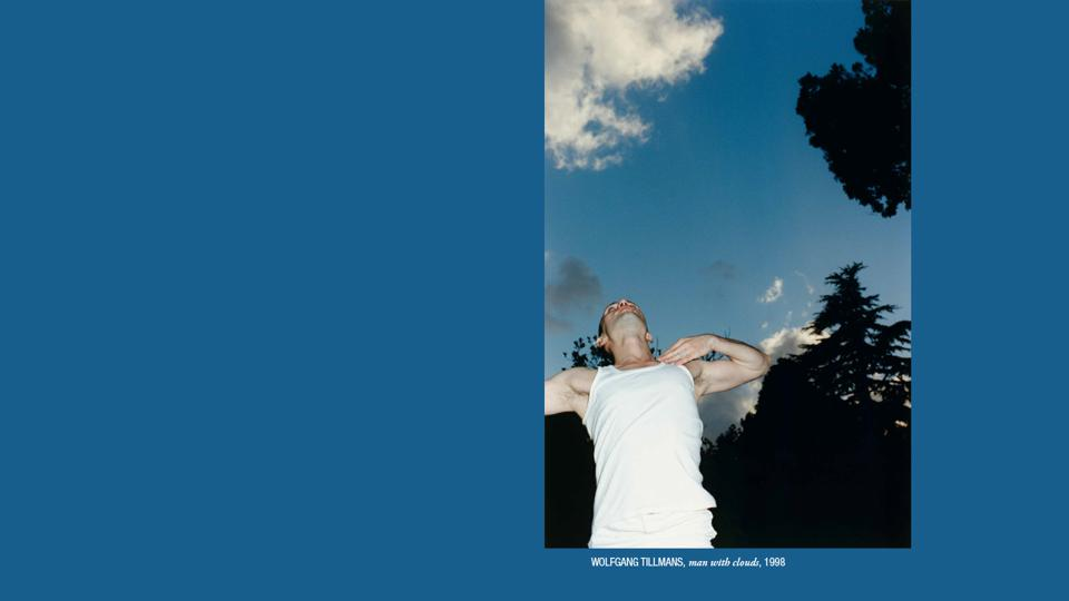 A young man in a white tank top looks into the sky dotted with clouds and pine tree tops