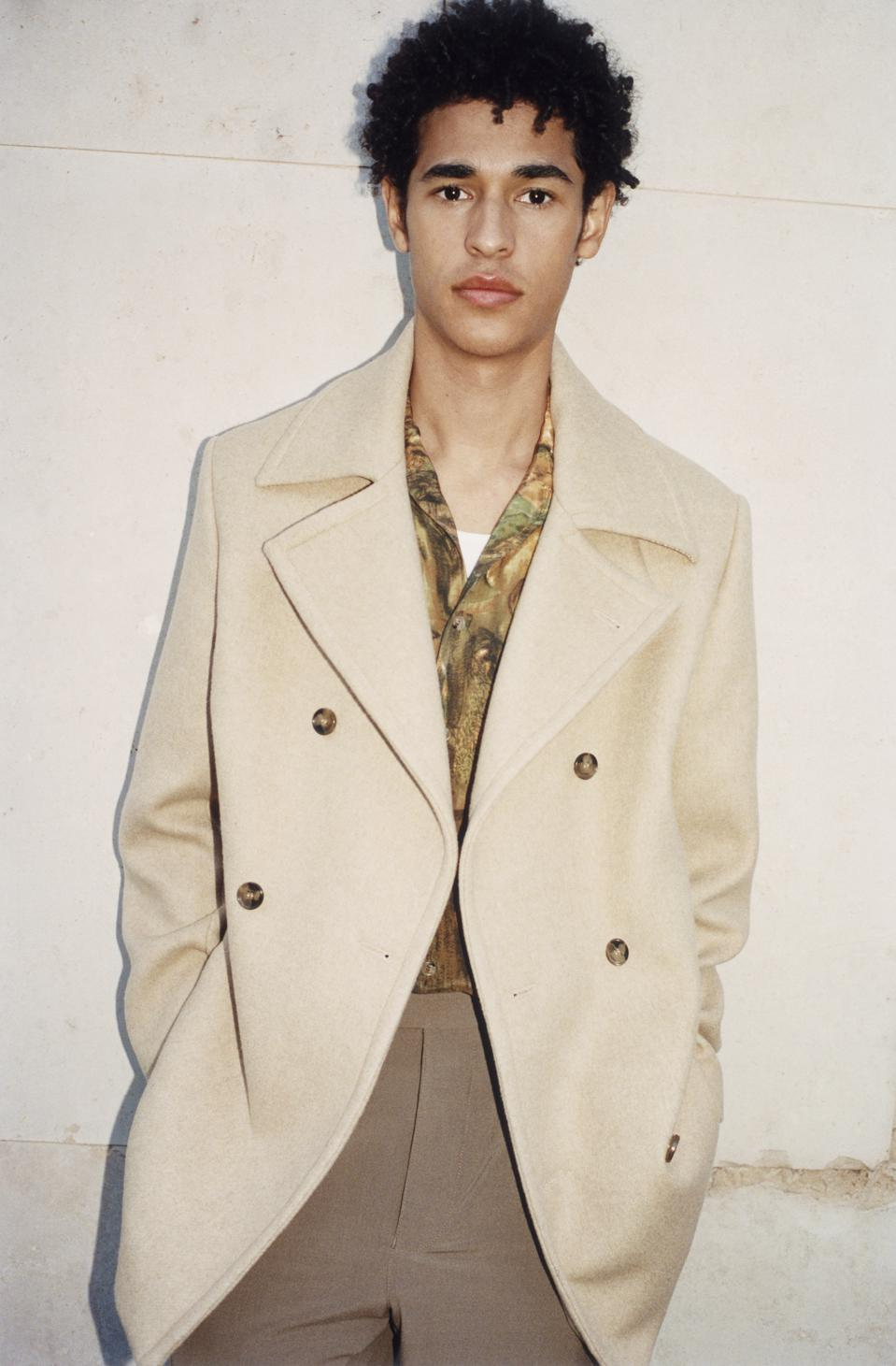 A mixed-race male model in his 20w models a tan overcoat, printed shirt and light brown pants from a sustainable brand