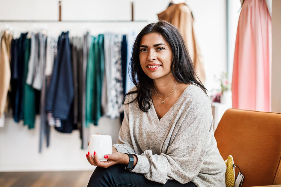Portrait Of Woman Drinking Coffee In Clothing Store