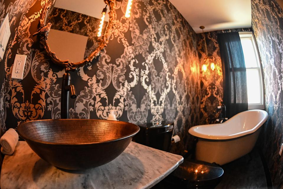 A gothic-inspired bathroom with copper sink, black toilet and white porcelain tub.