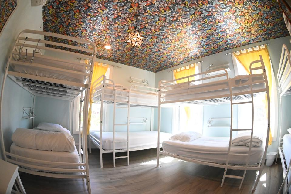A blue room with yellow curtains and three white bunk beds beneath a multicolored ceiling.