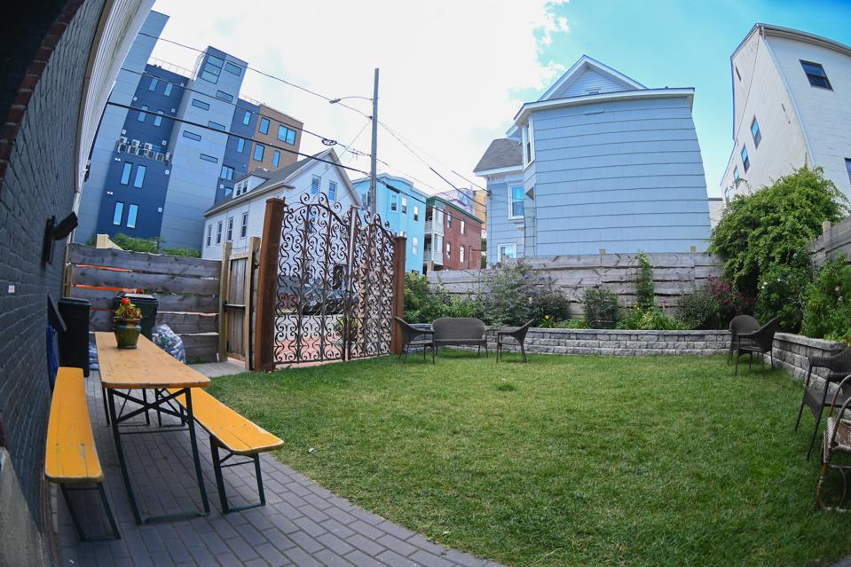 A small, square urban garden with a wrought iron fence and yellow picnic table.