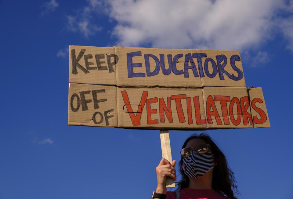 A protester holds a placard that says Keep Educators Off Of...