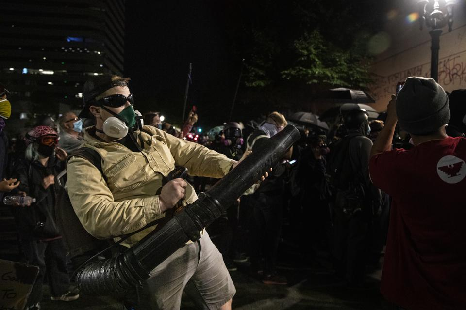 PORTLAND, OR - JULY 25:  A protester uses a leaf blower to dire