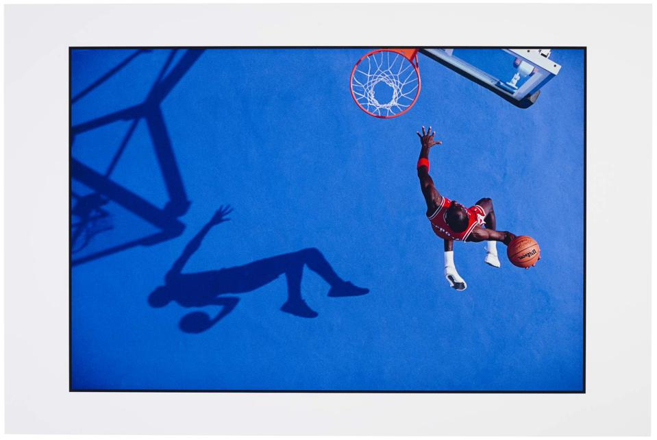 Photograph of Michael Jordan going up for a slam dunk with his shadow on blue pavement
