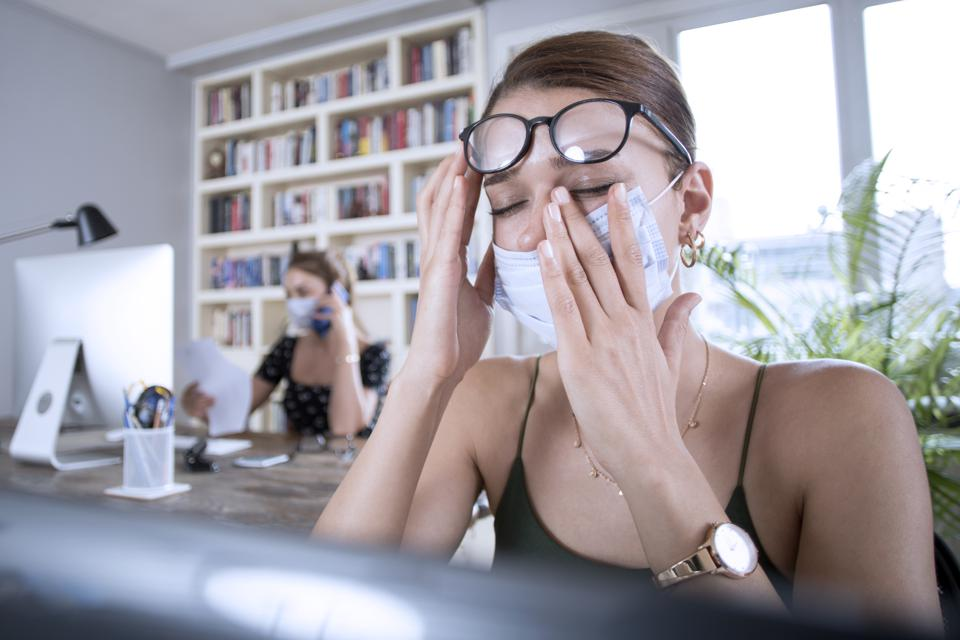 Woman rubbing her eyes at work while wearing a mask.