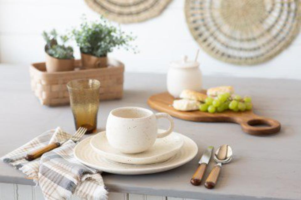 Cream-colored dinnerware, textiles, flatware and a cutting board from Longaberger's expanded product mix.