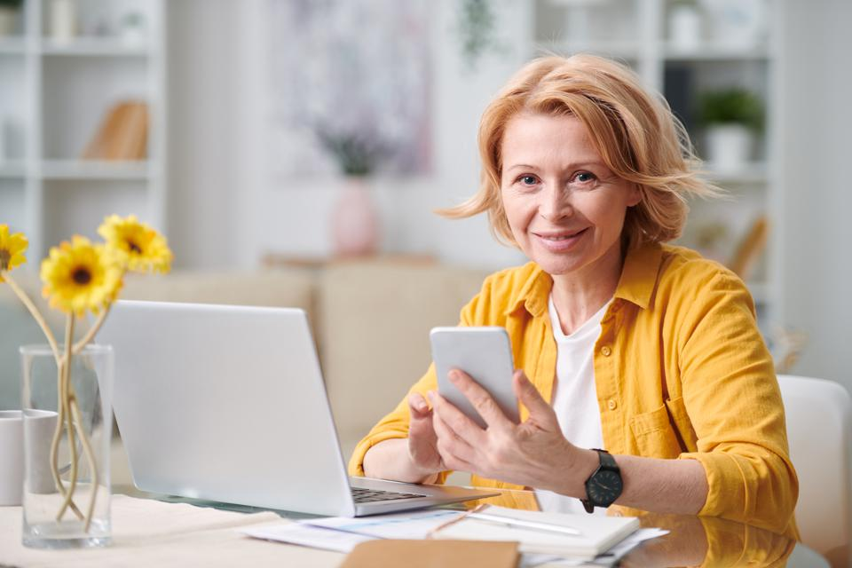 Smiling mature blond businesswoman with smartphone looking at you