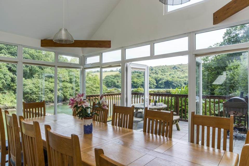 The conservatory opening onto a terrace, with all-around creek views