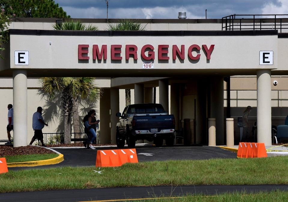 People are seen outside the entrance to the emergency room...