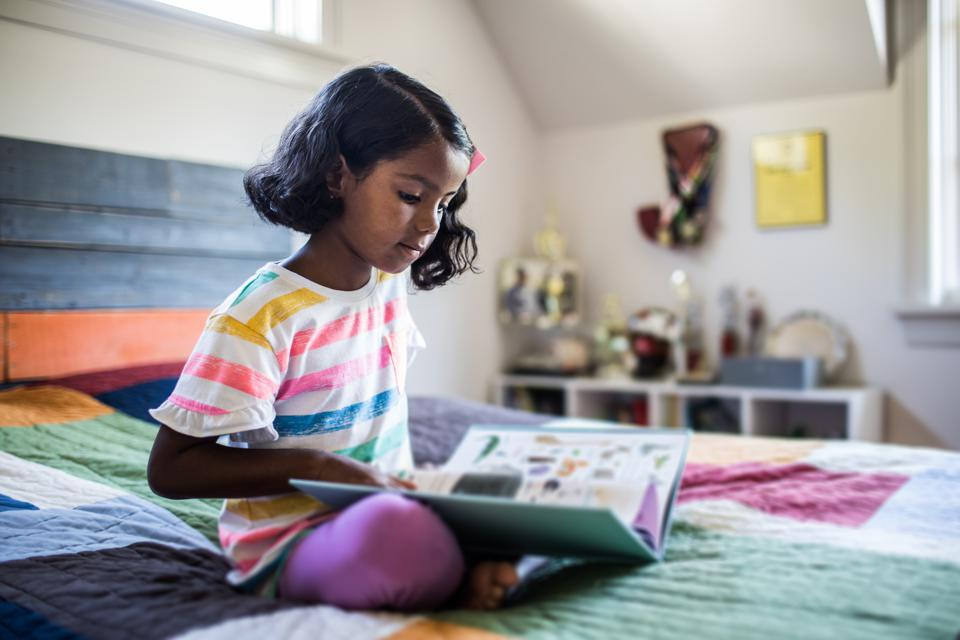 Girl reading book on her bed.