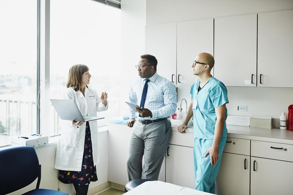 Female doctor leading medical team discussion in hospital exam room