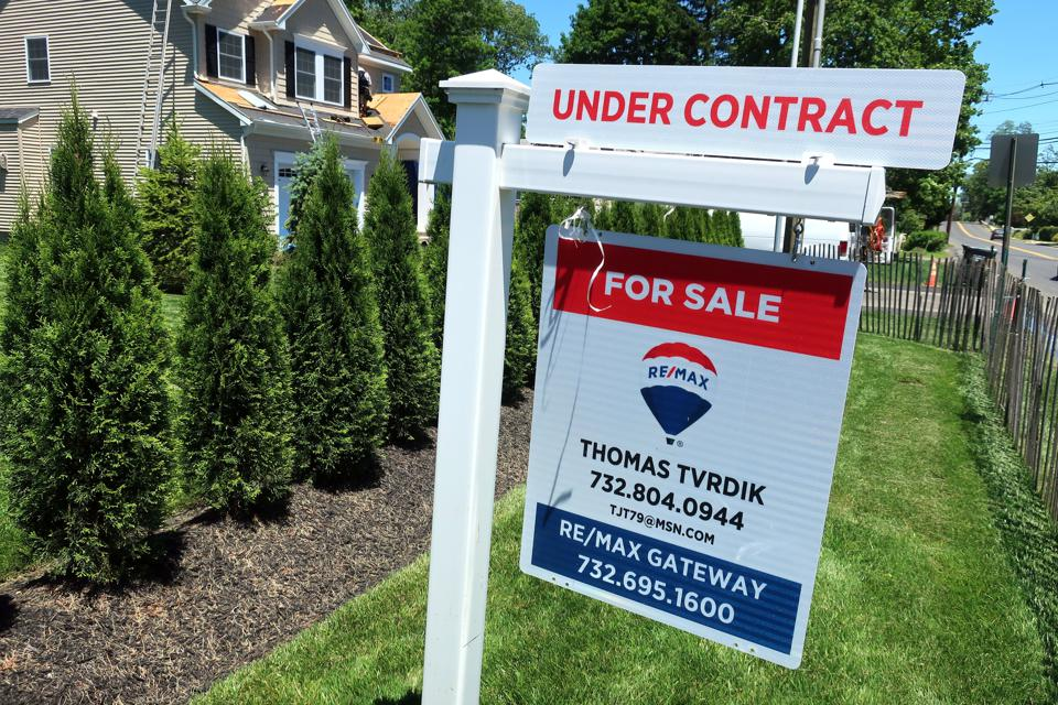An under contract placard has been added to a home for sale sign in Eatontown, N.J., June 14, 2018. (AP Photo/Ted Shaffrey)
