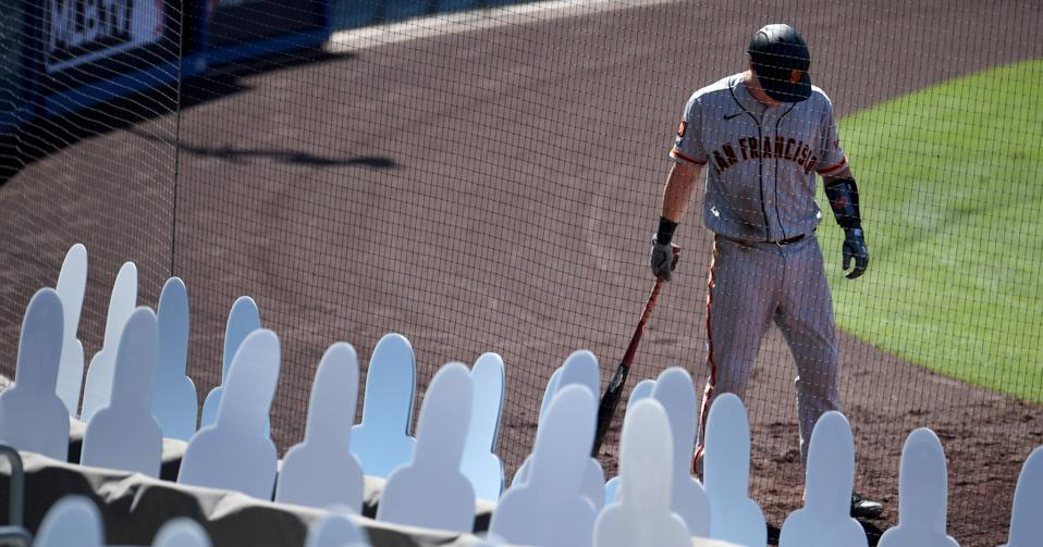 Tyler Heineman of the San Francisco Giants in front of cardboard cutouts of fans.