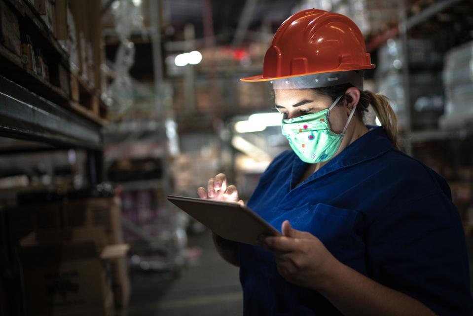Ritratto della maschera di protezione da portare della metà di donna adulta facendo uso della compressa digitale - lavorando al magazzino / all'industria