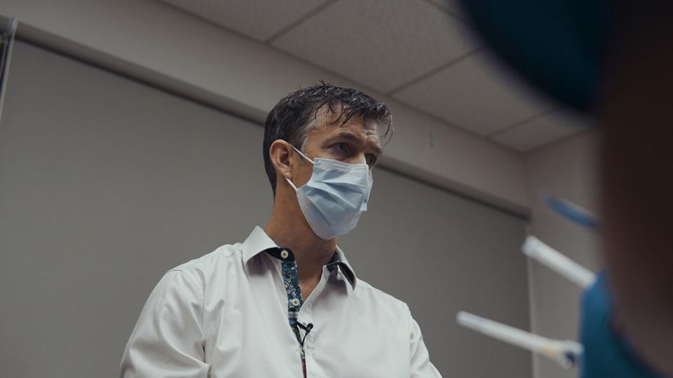 Dr. Matt Cook stands in an exam room speaking to an unseen patient wearing a surgical mask.