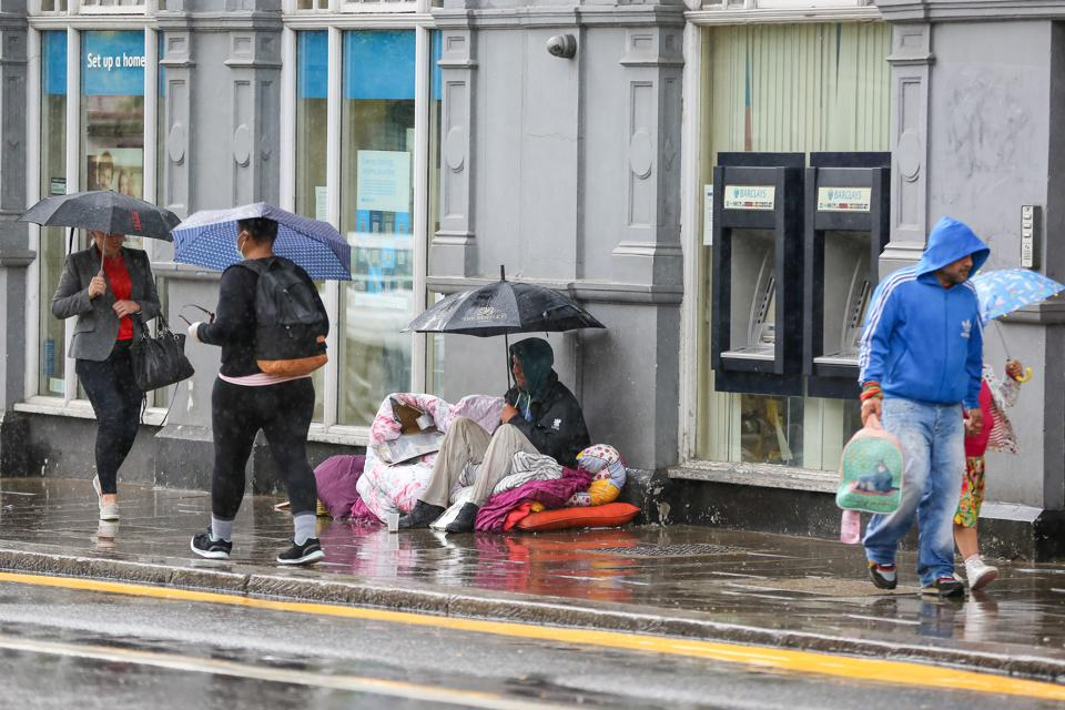 A homeless man and members of public shelter from the rain...
