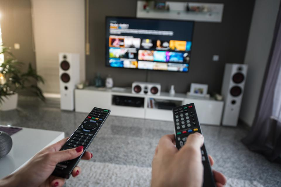 Man and woman with television remote control