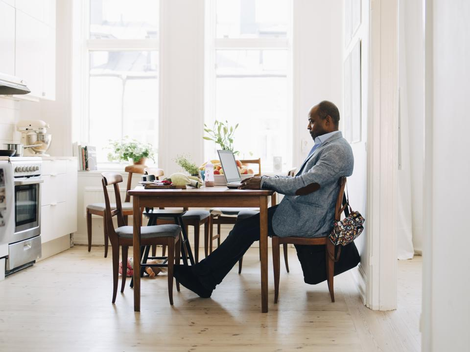 Full length of mature man working on laptop while sitting in kitchen at home