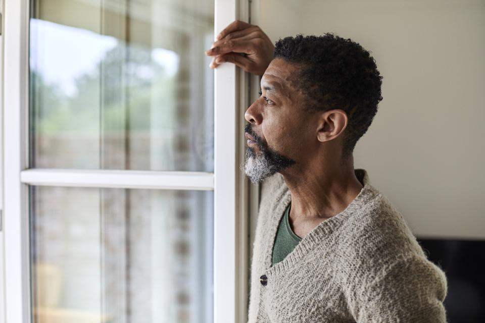Pensive man looking out of window