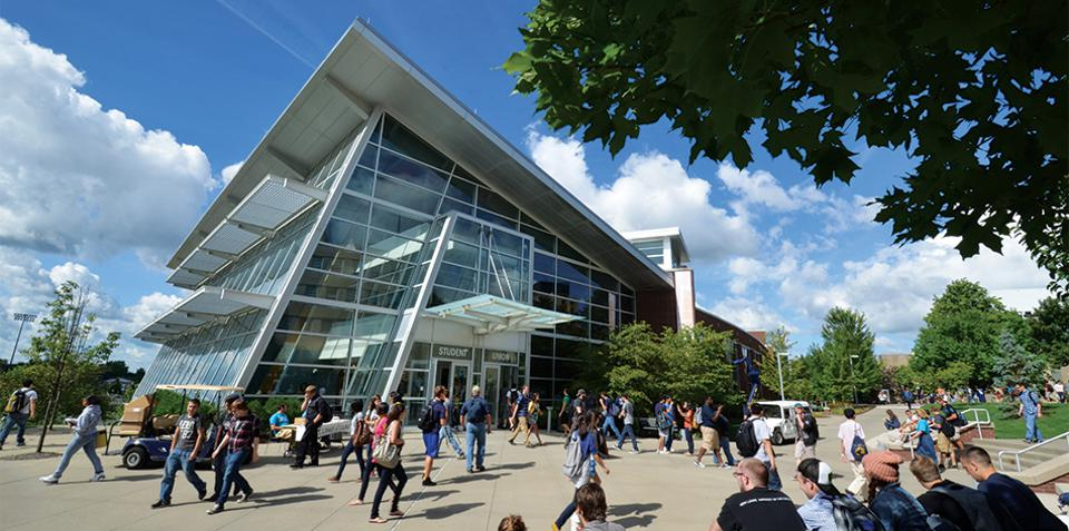 Modern, glass building on University of Akron campus, bustling with students.