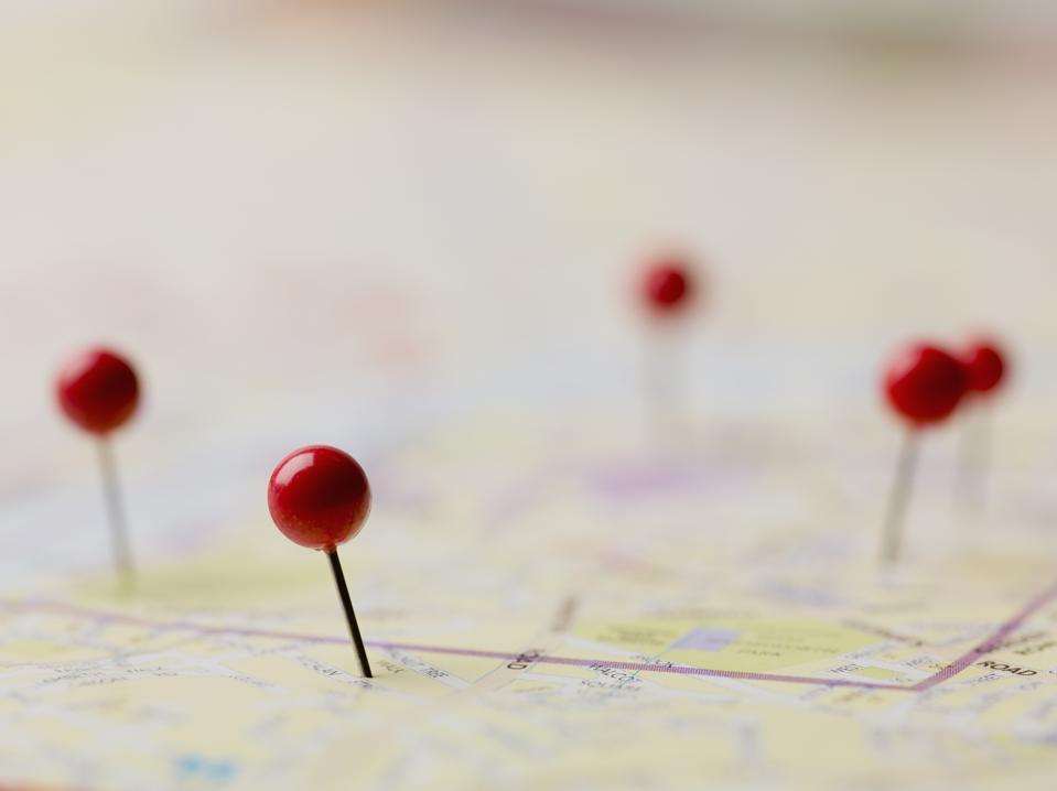 Red thumbtacks on map