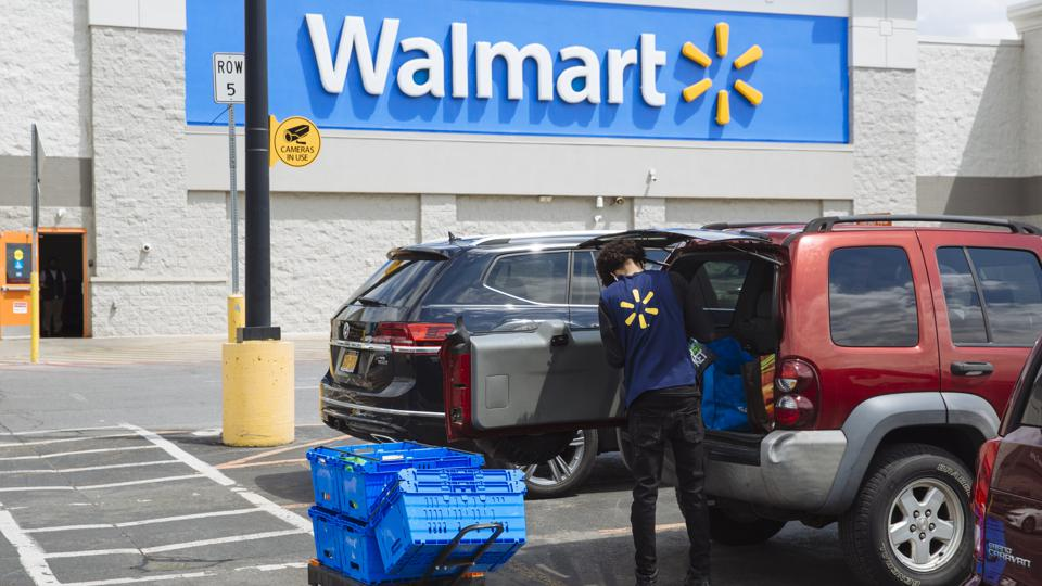 A worker delivers groceries to a customer's vehicle outside a Walmart Inc. store in Amsterdam, New York, U.S., on Friday, May 15, 2020.