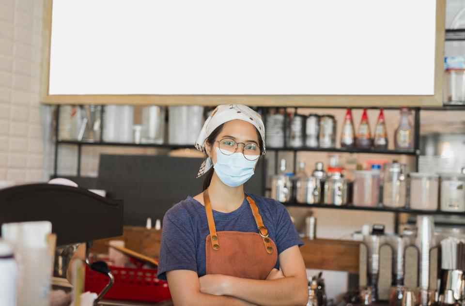 Women wearing protective mask standing in cafe during covid-19 preventing.