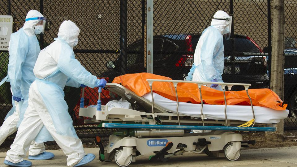 Medical works bring a deceased patient to a morgue.