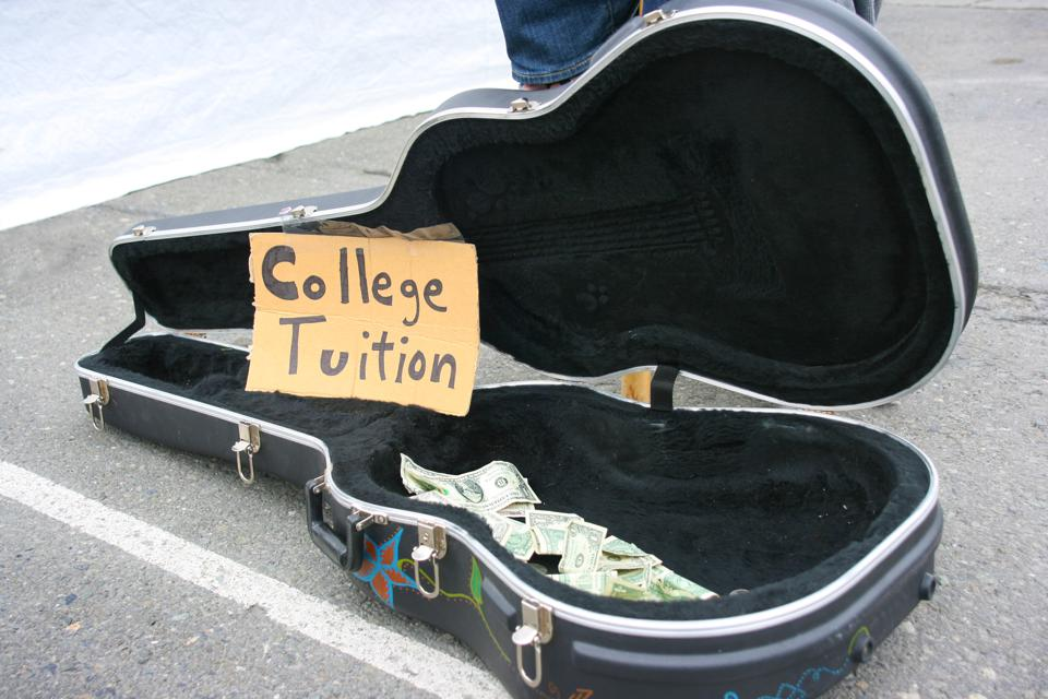 Guitar case open with money for tips with ″College Tuition″ sign