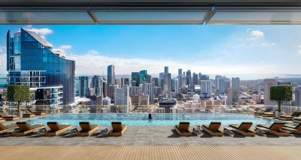 A rooftop infinity pool overlooks a city skyline.
