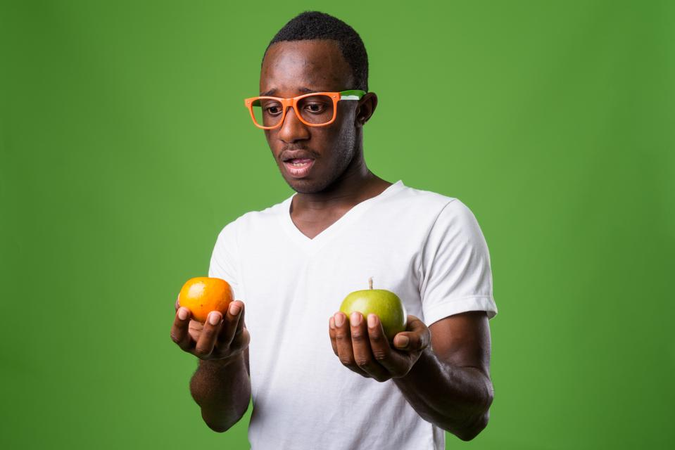 Studio shot of young African man wearing white shirt against green background
