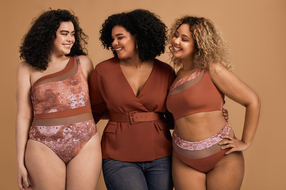 3 women, two in bathing suits and one wearing jeans and a top, smiling
