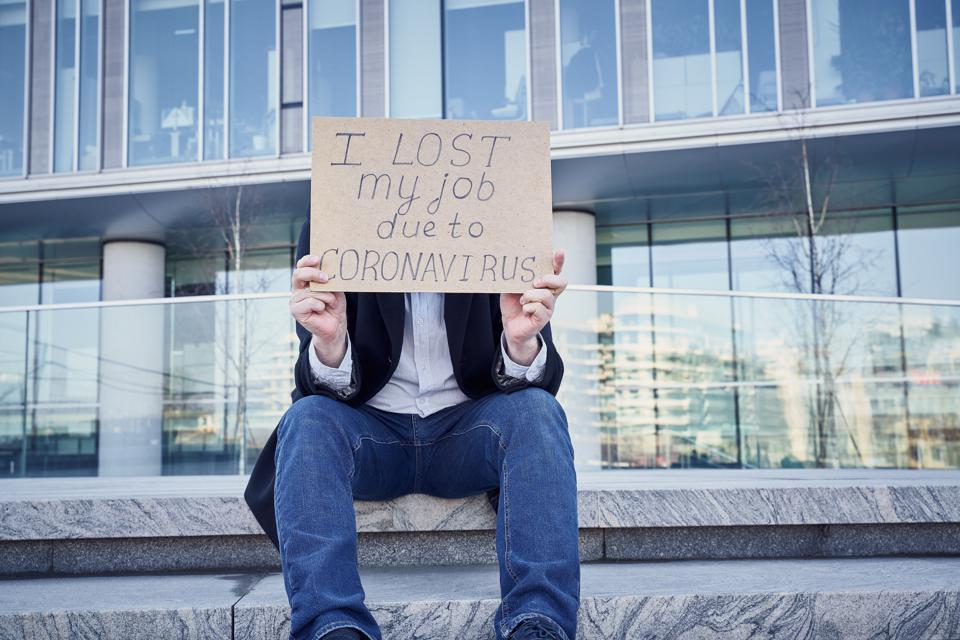 Job loss due to COVID-19 virus pandemic concept. Unrecognizable man holds sign ″I lost my job″