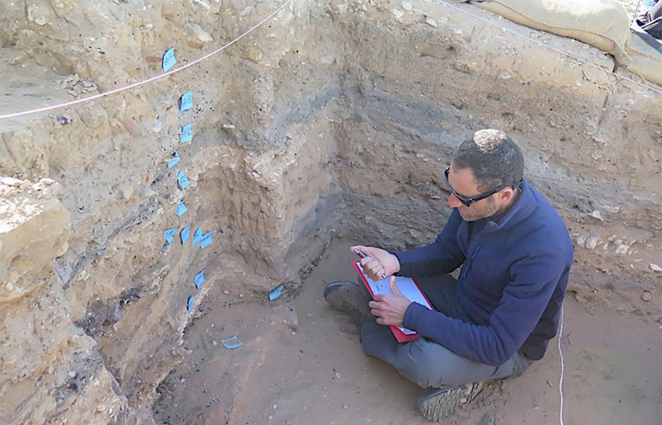 A researcher studying sedimentary layers preserved in a garbage pit of the ancient city of Elusa in modern Israel.