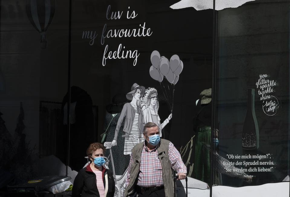 A couple wearing face masks outside a boutique in Vienna, Austria