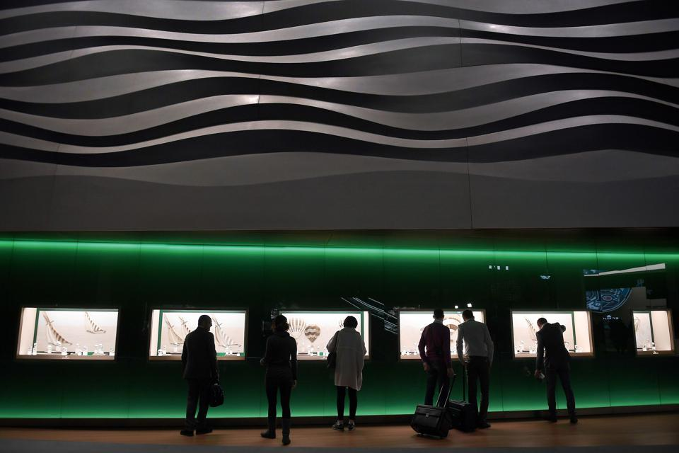 Visitors are contemplating the windows of a luxury watch brand at the Baselworld fair.