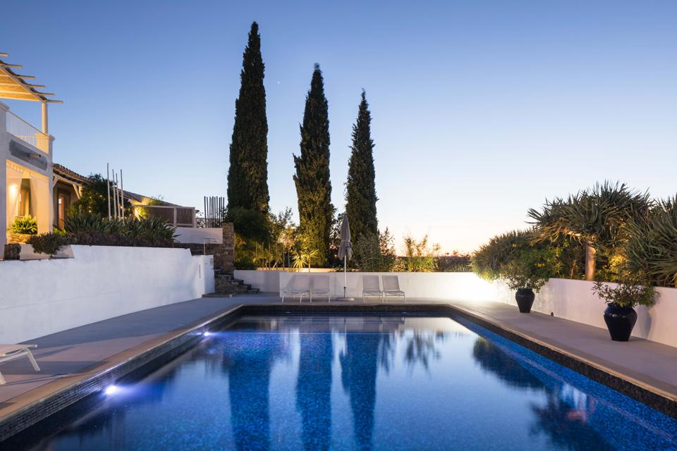 The swimming pool at Farmhouse of the Palms in Portugal is illuminated at sunset.