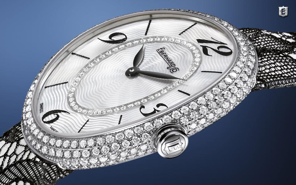 The Eberhard & Co Gilda is paved with diamonds, has a mother of pearl dial and black lace strap