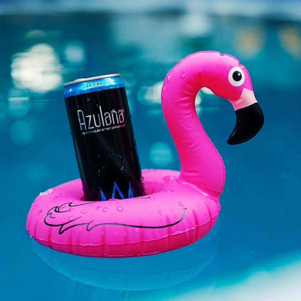 a can floating in a flamingo drink holder.