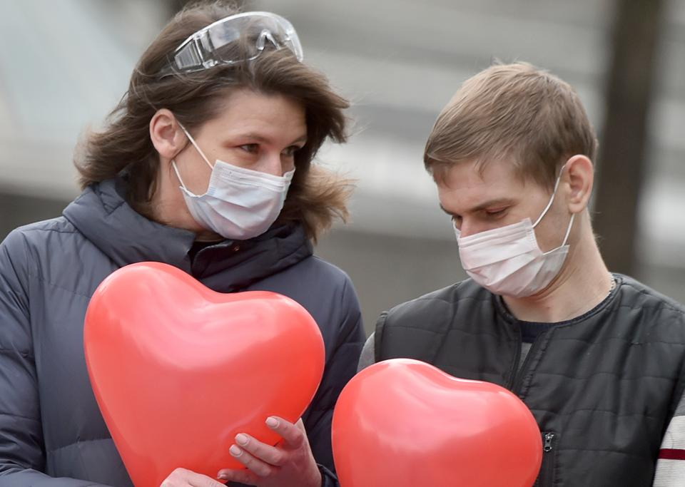 A couple wearing face masks hold love heart shaped balloons in Europe