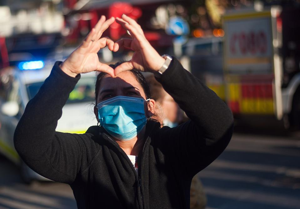 A woman wearing a face mask in Europe making a heart shape for love