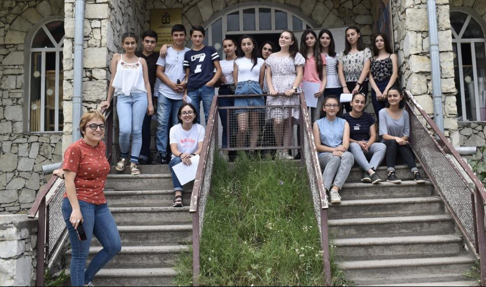 A group of students sitting and standing on stairs as part of Girls in Tech, Armenia with Seda Papoyan in the forefront
