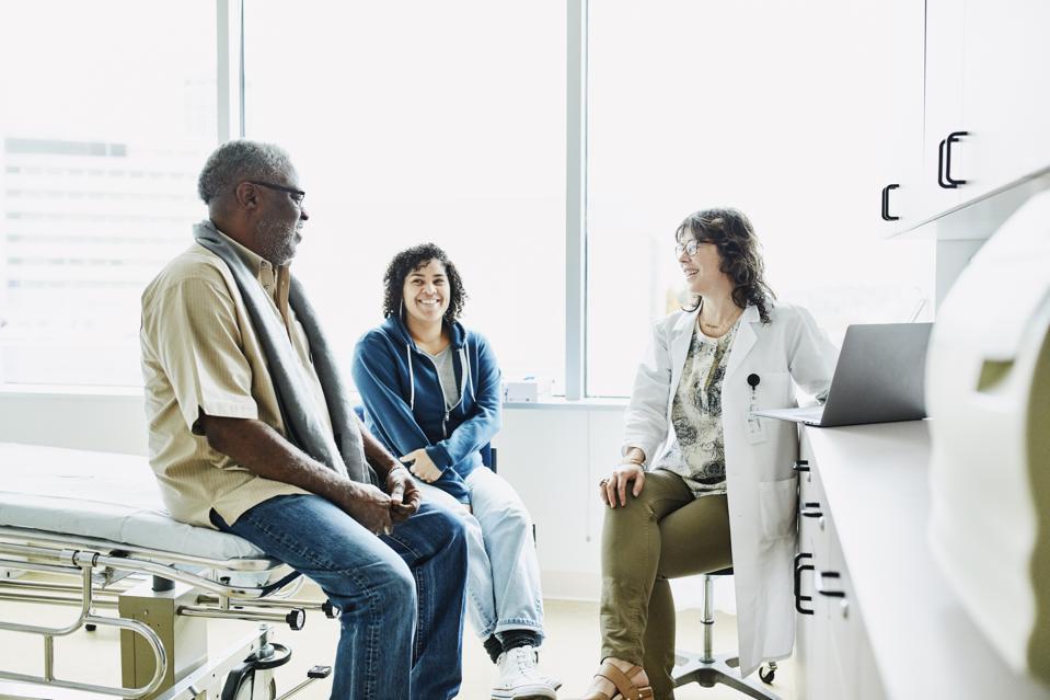 Smiling female doctor consulting with senior male patient et adulte fille dans la salle d'examen