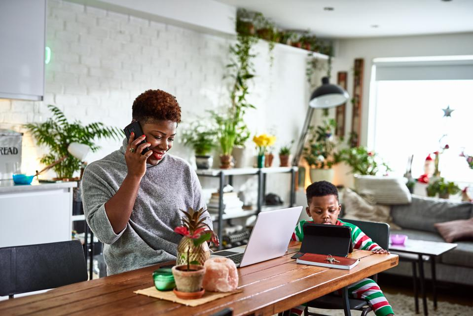 Mother working from home with son.