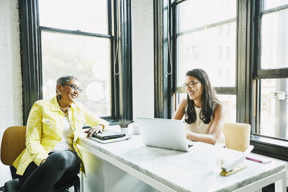 Smiling businesswoman in discussion with client at desk in office